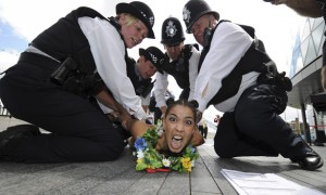 A Femen movement protestor is detained by police officers in London during a naked protest about Islamic states taking part in the Olympics