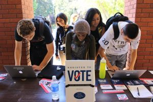 Young voters register at a table. Don't let their looks fool you, these new voters will someday mature into scared, old people.